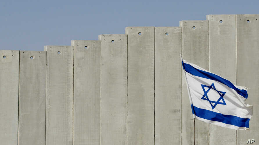An Israeli flag is planted in front of Israel's separation barrier in the West Bank village of Abu Dis, on the outskirts of Jerusalem, Wednesday, July 7, 2004. The International Court of Justice in the Hague is to rule Friday on the legality of a bar...