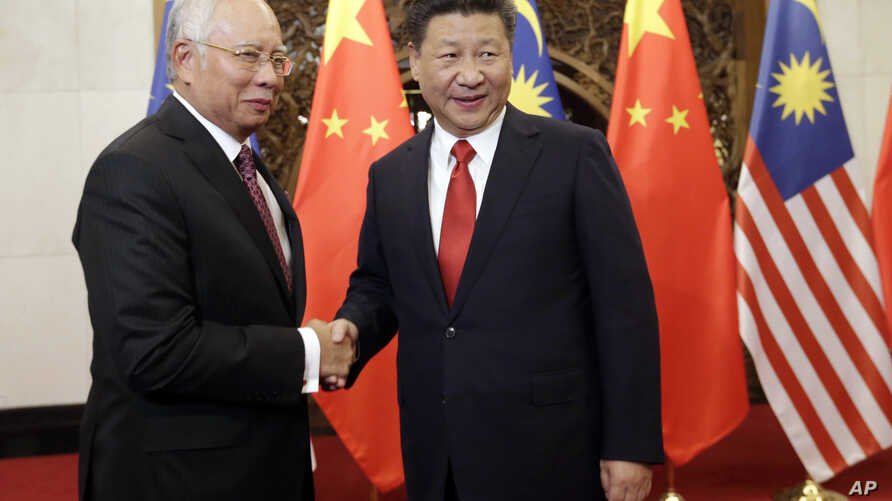 FILE - Malaysian Prime Minister Najib Razak, left, poses with Chinese President Xi Jinping for a photo prior to their meeting at Diaoyutai state guesthouse in Beijing, Nov. 3, 2016.