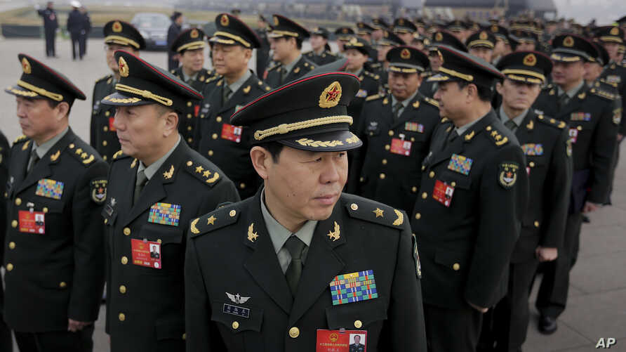 Delegates from China's People's Liberation Army (PLA) stand in line as they arrive at the Great Hall of the People to attend a session of National People's Congress in Beijing, March 4, 2016.