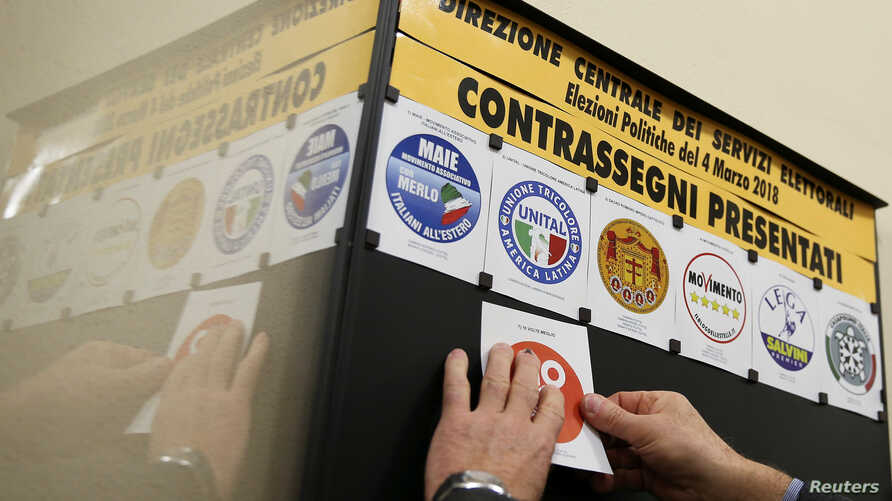 A man posts symbols of parties that will run in the country's March 4 election at the Ministry of the Interior palace in Rome, Italy, Jan. 19, 2018.