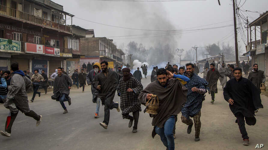 FILE - Kashmiri villagers run for cover from tear gas shells and pellets fired at by Indian police during a protest near the funeral of Rayees Ahmad Dar, a suspected militant of Lashkar-e-Taiba in Kakpora village south of Srinagar, Indian controlled
