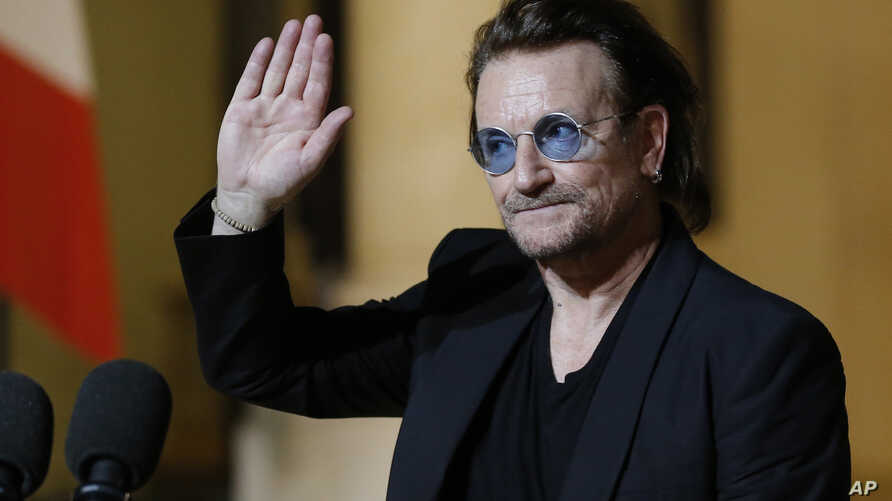 FILE - In this Monday, Sept. 10, 2018 file photo, U2 singer Bono waves good-bye to the media after a meeting with French President Emmanuel Macron at the Elysee Palace in Paris, France. Trump has sought to slash hundreds of millions from U.S. funding