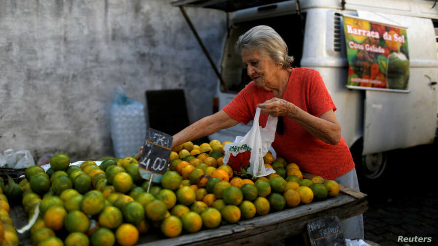 FILE - A customer selects oranges at a street market in Rio de Janeiro, Brazil, May 6, 2016. In an attempt to gain extra revenue, Brazil is poised to offer amnesty to Brazilians who return assets they hold abroad.