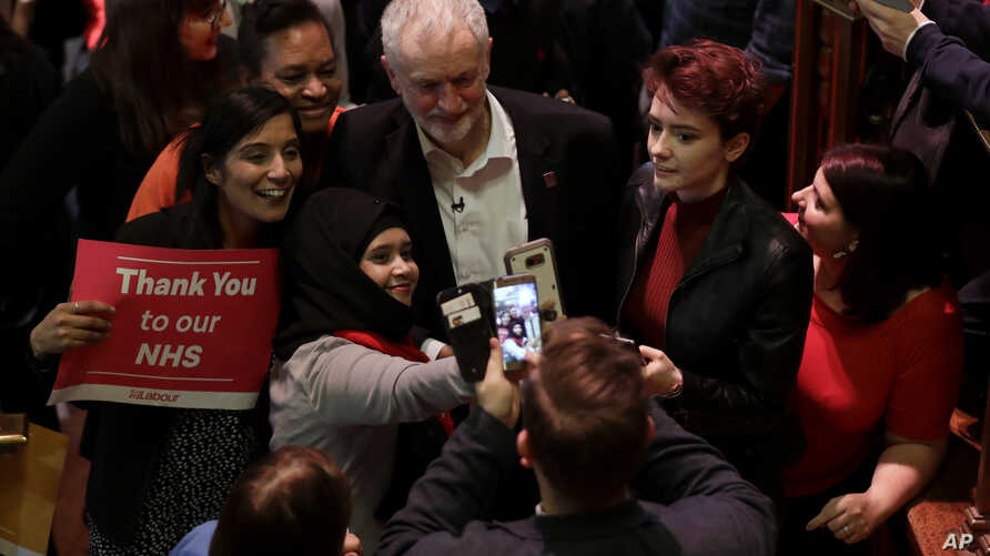 The leader of Britain's opposition Labour party Jeremy Corbyn poses with supporters after his speech at a rally to demand the government introduce an emergency budget for the National Health Service (NHS) to end a winter crisis, at Methodist Central