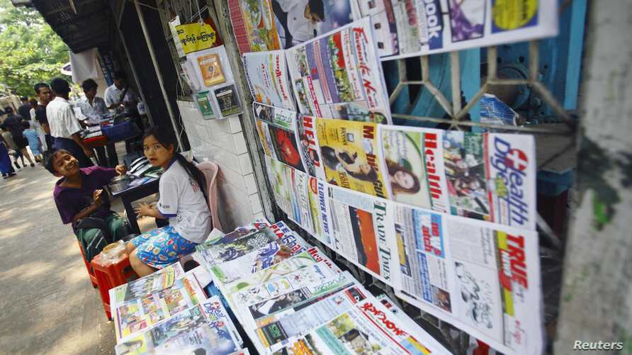 A girl selling weekly journals waits for customers in Rangoon, Burma, April 2, 2012.