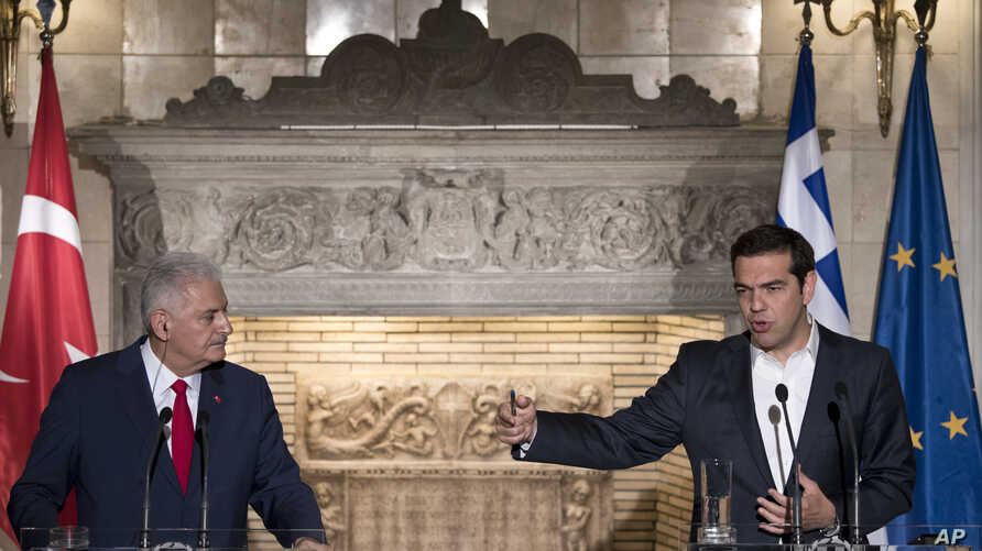 Greek Prime Minister Alexis Tsipras, right, answers a question during a press conference with his Turkish counterpart Binali Yildirim after their meeting in Athens, June 19, 2017.