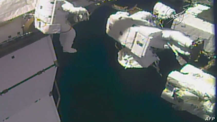 This NASA TV video grab image obtained on Oct. 10, 2017 shows astronauts outside the International Space Station to complete repairs to the station's robotic arm. Randy Bresnik is leading the outing, accompanied by Mark Vande Hei. (AFP PHOTO / NASA T