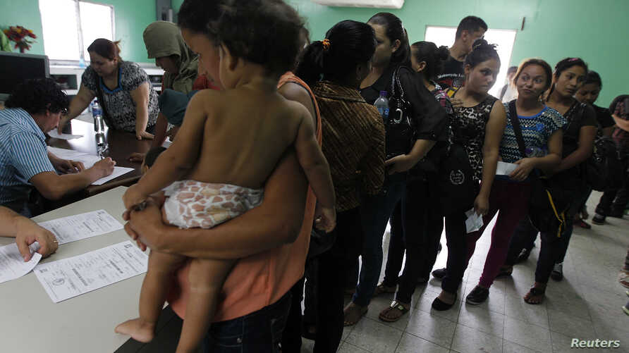 FILE - Women and their children, many who had hoped to reach the U.S., wait in line to register at the Honduran Center for Returned Migrants after being deported from Mexico, in San Pedro Sula, northern Honduras June 20, 2014.