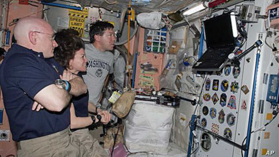 Astronauts Scott Kelly, left, Expedition 26 commander; Cady Coleman, center, Expedition 26 flight engineer; and Michael Barratt, STS-133 mission specialist, watch a monitor in the International Space Station while space shuttle Discovery remains dock