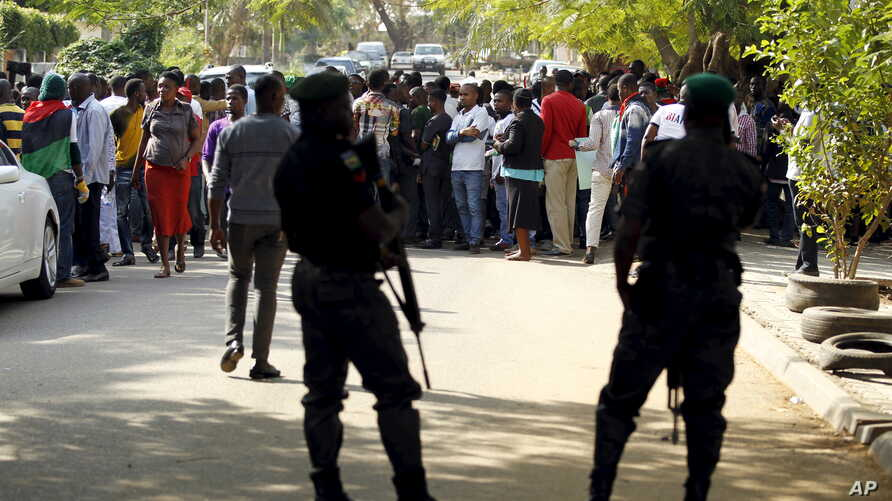 Policemen stand guard as supporters of Indigenous People of Biafra leader Nnamdi Kanu rallies before appearance in magistrate court, Abuja, Nigeria, Dec. 1, 2015.