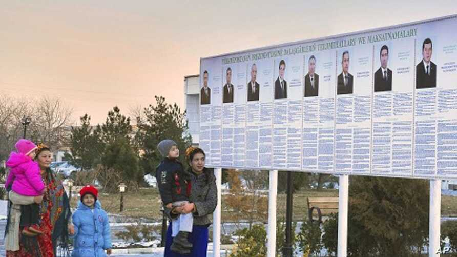 Residents look at a presidential election poster depicting the candidates in Ashgabat, Turkmenistan, February 7, 2012.