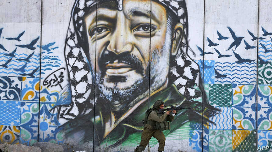 A member of the Israeli border guards looks through the scope of an assault rifle as he stands by a mural showing a graffiti image of late Palestinian leader Yasser Arafat, at the Qalandiya checkpoint near the West Bank city of Ramallah.