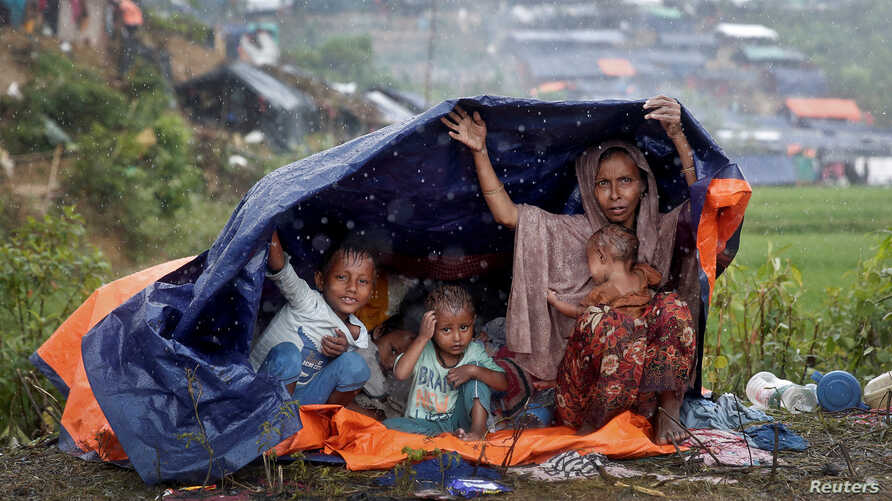Rohingya refugees shelter from the rain in a camp in Cox's Bazar, Bangladesh, Sept. 17, 2017.