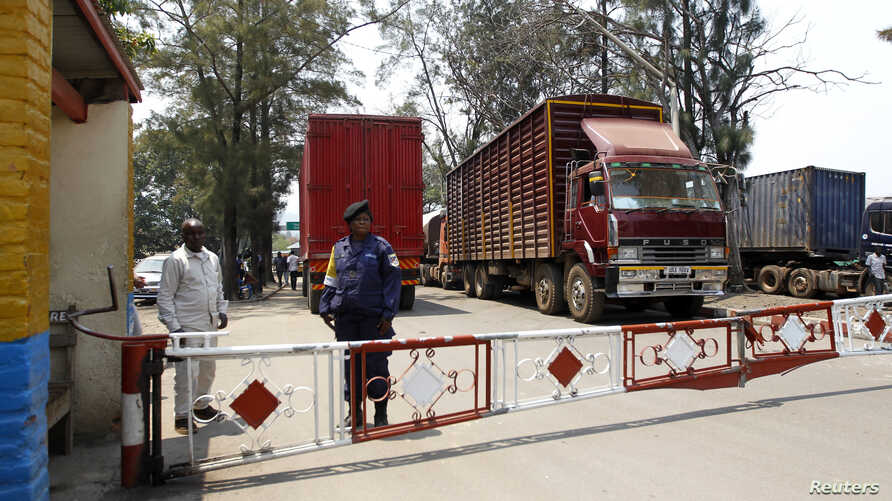 FILE - A Congolese policewoman and customs officials secure the gate barriers at their border crossing point with Rwanda in Goma town in the eastern Democratic Republic of Congo, Aug. 29, 2013.