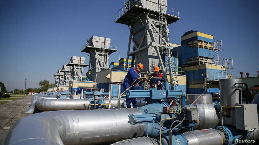 Workers stand near pipes at a gas compressor station near Uzhhorod May 21, 2014. Russia has said state-controlled exporter Gazprom will not supply transit nation Ukraine with gas for its own use in June if Kiev fails to pay in advance and has warned
