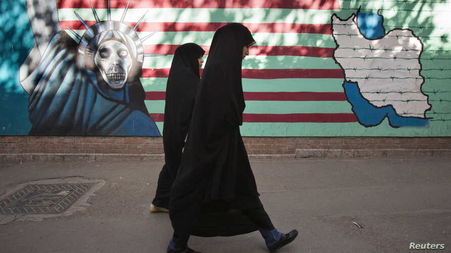 Iranian women walk past an anti-U.S. mural on the wall of the former U.S. embassy in Tehran, Oct. 12, 2011.