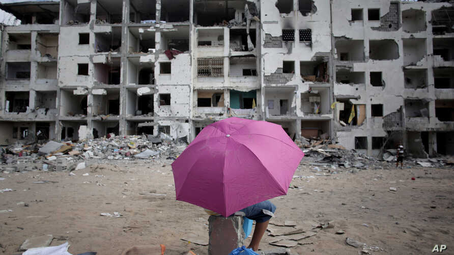 A Palestinian boy holds an umbrella as he rests in front of the damaged Nada Towers residential neighborhood in the town of Beit Lahiya, northern Gaza Strip, Monday, Aug. 11, 2014.