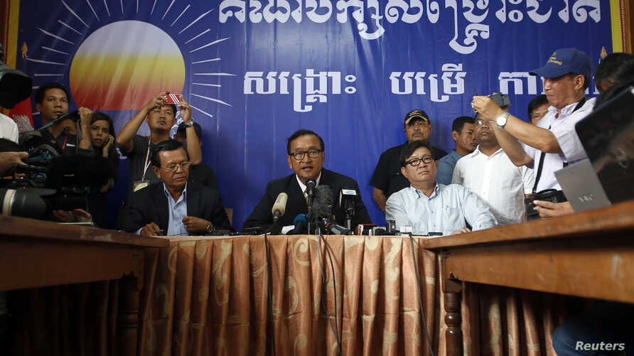 Sam Rainsy (C), president of the Cambodia National Rescue Party (CNRP) addresses reporters at his party's headquarters in Phnom Penh, Cambodia, July 29, 2013.
