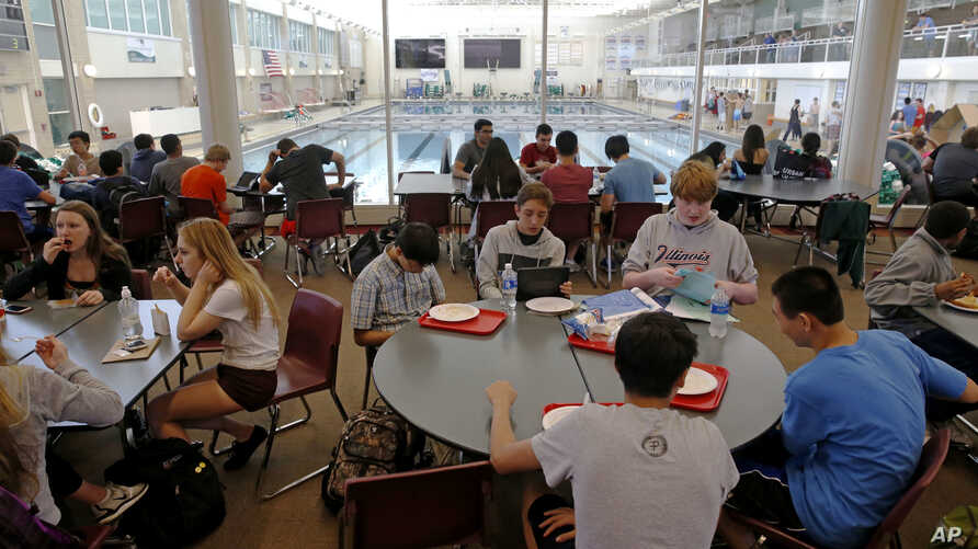 FILE - Students gather between classes in a lounge area overlooking an Olympic-size pool at Stevenson High School in Lincolnshire, Ill., May 24, 2016.