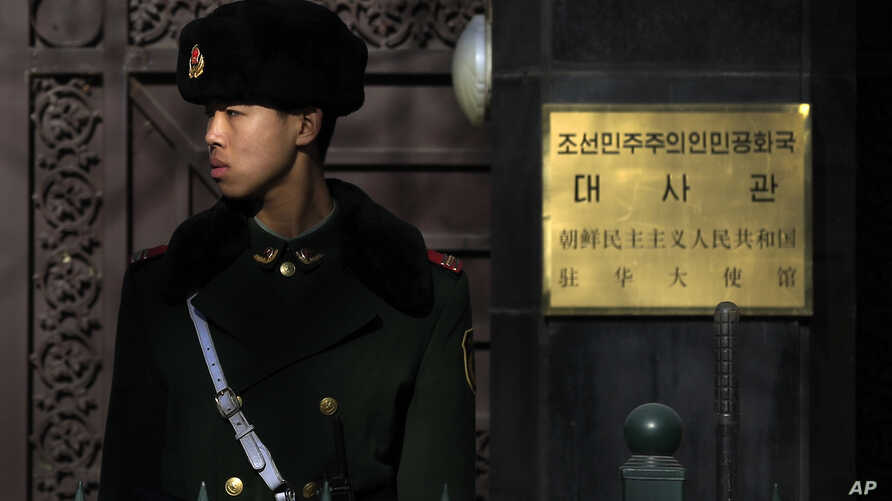 A Chinese paramilitary policeman stands guard outside the North Korean Embassy in Beijing, Jan. 6, 2016.