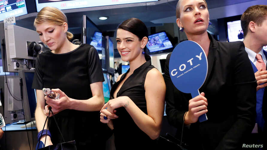 FILE - Models gather at a trading post on the floor of the New York Stock Exchange for the IPO of Coty Inc., June 13, 2013.