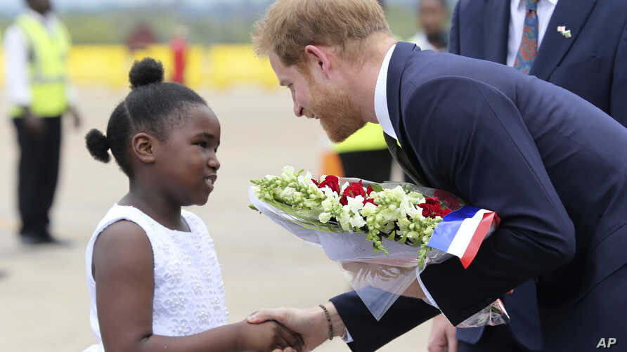 Britain's Prince Harry receives flowers from a girl upon his arrival at Kenneth Kaunda airport in Lusaka, Nov. 26, 2018.
