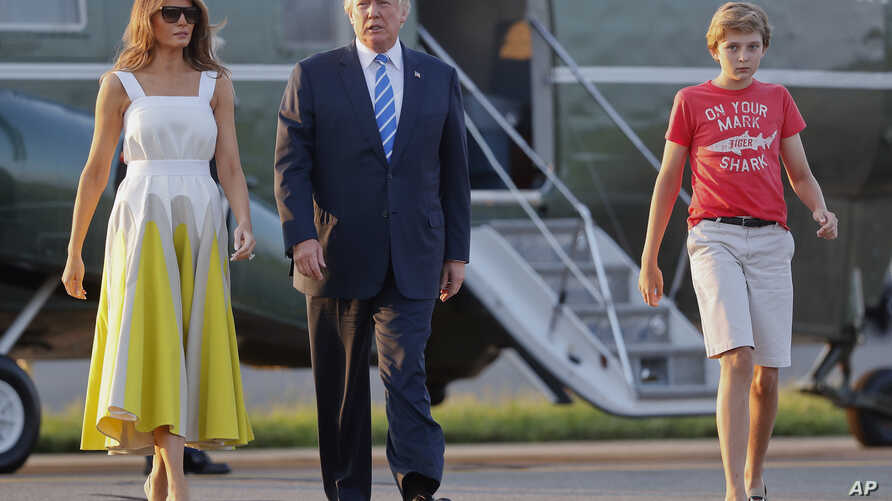 President Donald Trump, first lady Melania Trump and son Barron Trump walk across the tarmac to board Air Force One at Morristown Municipal Airport, Aug. 20, 2017, in Morristown, N.J.