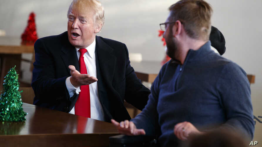 """President Donald Trump reacts after seeing a """"Trump"""" sticker as he meets retired U.S. Marine Corps Sgt. John Peck and his wife, Jessica, as Trump visits with wounded service members and their families at Walter Reed National Military Medical Center,"""