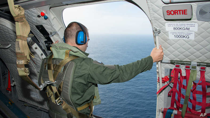 In this photo released on Aug. 7, 2015 by the French Army Communications Audiovisual office (ECPAD), a crew member looks out of the airplane door taking part in the search for wreckage from the missing MH370 plane off the coasts of the French island