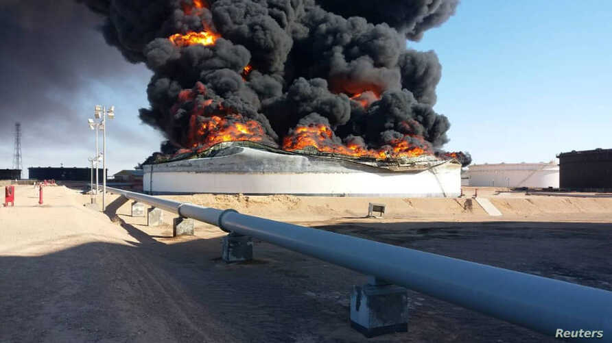 Smoke and flame rise from an oil storage tank that was set on fire amid fighting between rival factions at Ras Lanuf terminal, Libya, in this handout picture released June 18, 2018.