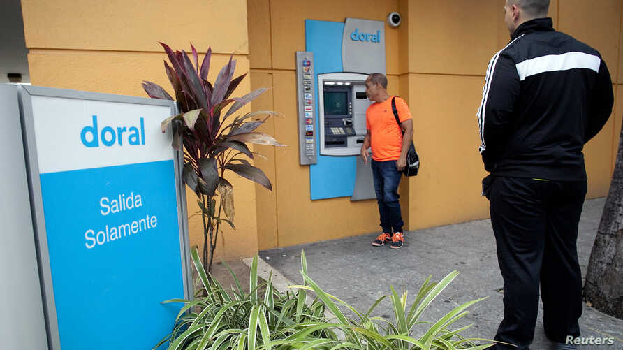 FILE - A man looks at the screen of an ATM of the failed Doral Bank in San Juan, Puerto Rico, February 27, 2015.