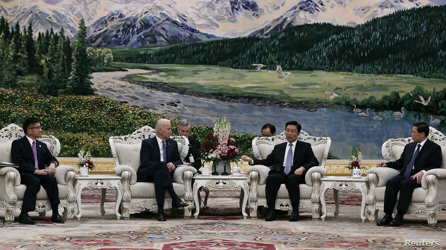 U.S. Vice President Joe Biden (center, L) talks with Chinese Vice President Li Yuanchao (center, R) after a welcoming ceremony at the Great Hall of the People in Beijing, Dec. 4, 2013.