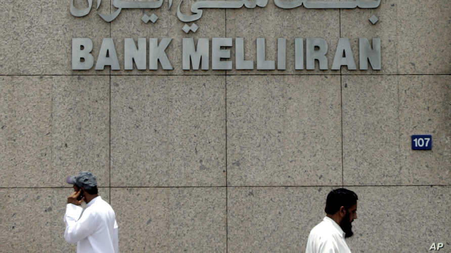 FILE - Two men pass by the main branch of Bank Melli Iran, the National Bank of Iran in Dubai, United Arab Emirates, July 1, 2008.