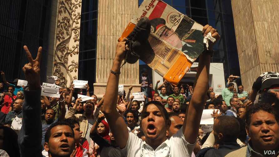 Holding a picture of the Egyptian president, a protester also raises his shoe, a symbol of disrespect in the Arab World in downtown Cairo, April 15, 2016. (VOA/H. Elrasam)