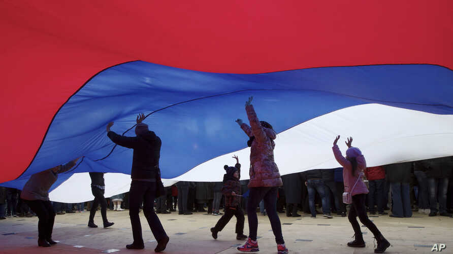 People stand under the giant national flag during the Vesna (Spring) festival commemorating the annexation, in Moscow, Russia, March 18, 2017.
