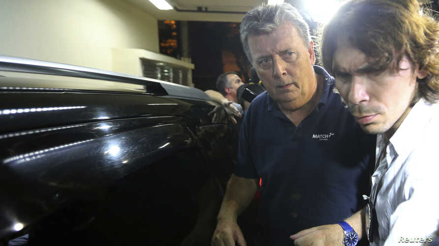Ray Whelan (L), of Switzerland-based Match Services, arrives at a police station after being arrested in connection with the illegal resale of tickets at the World Cup, in Rio de Janeiro, July 7, 2014.