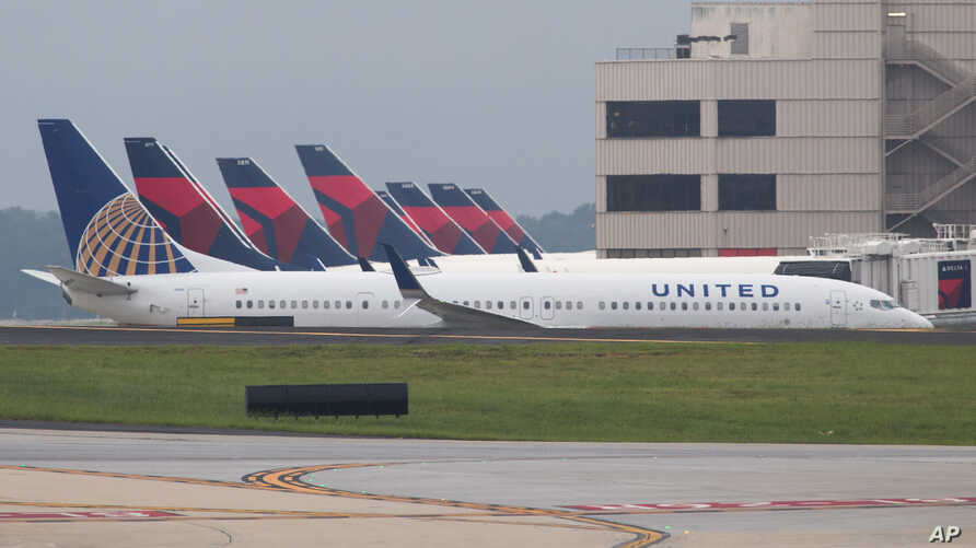 A United Airlines plane passes Delta planes that are parked at gates at Atlanta's Hartsfield International Airport in Atlanta, Aug. 8, 2016.