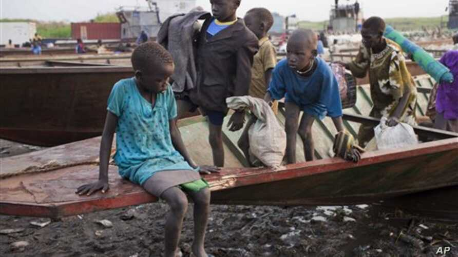 A group of displaced brothers and sisters cautiously disembark from a boat that has just carried them across the Nile to a village in Awerial, which has received tens of thousands of displaced people who crossed the Nile river by boat to flee the rec...