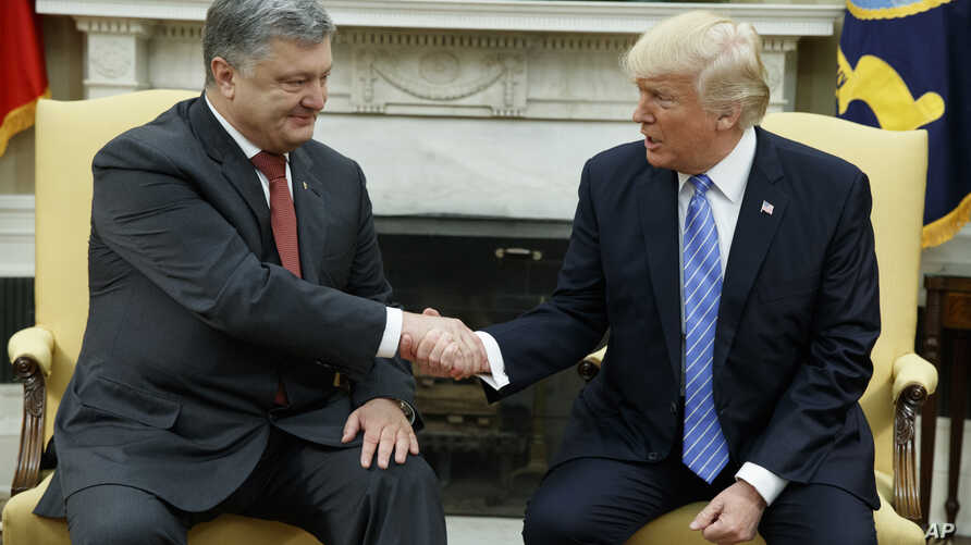 President Donald Trump, right, shakes hands with Ukrainian President Petro Poroshenko during a meeting in the Oval Office of the White House, June 20, 2017, in Washington.