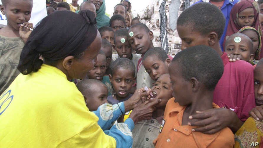 FILE - A World Health Organization (WTO) official gives a dose of polio vaccine to Somali children in Tosweyn village, in the Baidoa region, Somalia, Sept. 12, 2000.