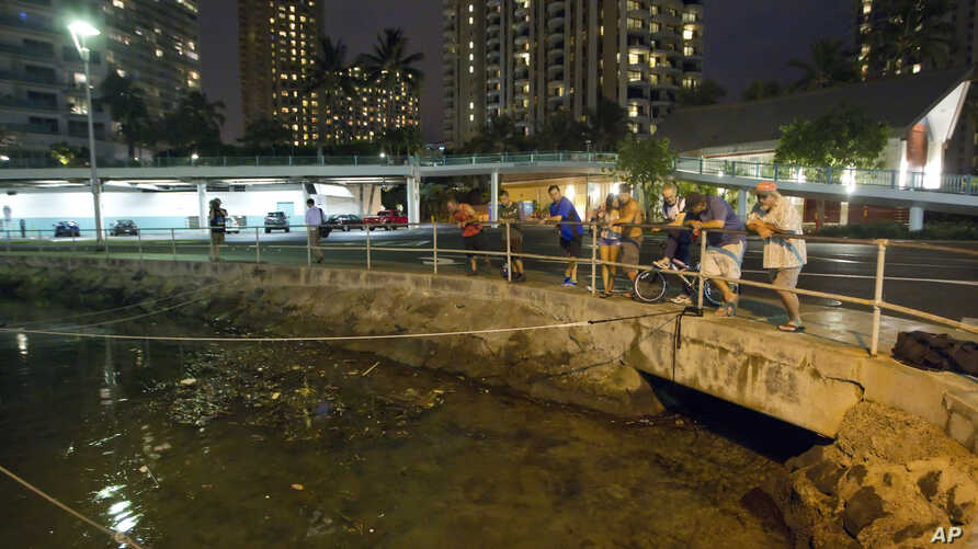 Visitors and Oahu residents watch the water level in the Ala Wai Harbor waiting for the arrival of a tsunami Saturday, Oct. 27, 2012, in Honolulu.
