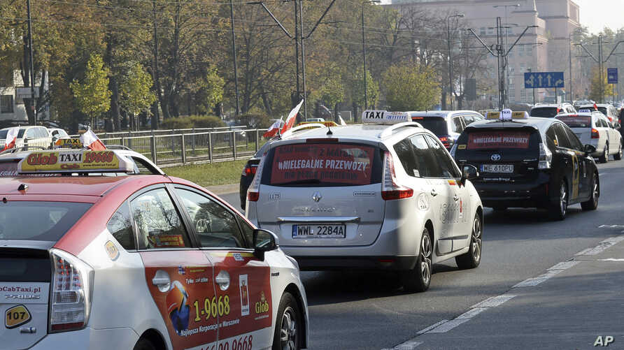Taxi drivers drive slowly through the capital city downtown causing some traffic jams in protest against low earnings and competition from unlicensed companies like Uber, in Warsaw, Oct. 18, 2018.