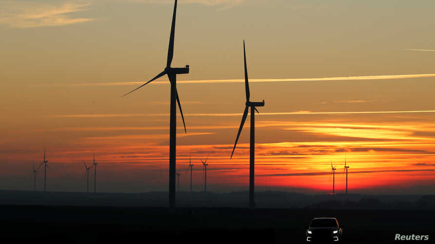 Power-generating windmill turbines are pictured at sunset at a wind park in Fins near Cambrai, France, Feb. 5, 2019.