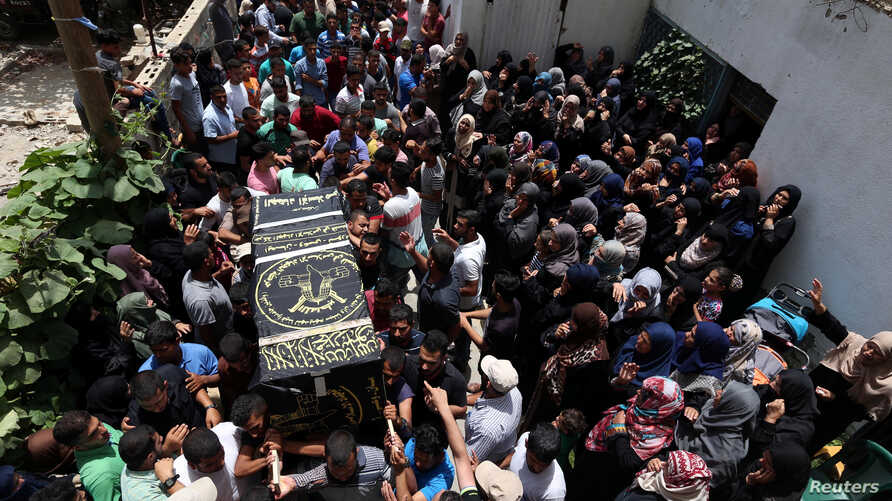 Mourners carry a casket containing the body of a Palestinian Islamic Jihad militant, who was killed in Israeli tank shelling, during his funeral in the southern Gaza Strip, May 27, 2018.