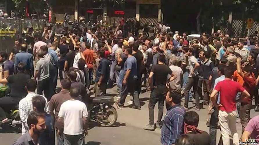 In this picture taken by a citizen journalist, Iranian security forces dressed in black confront anti-government protesters in Iran's third-largest city, Isfahan, during demonstrations that began on July 31, 2018 and continued for a second day on Aug