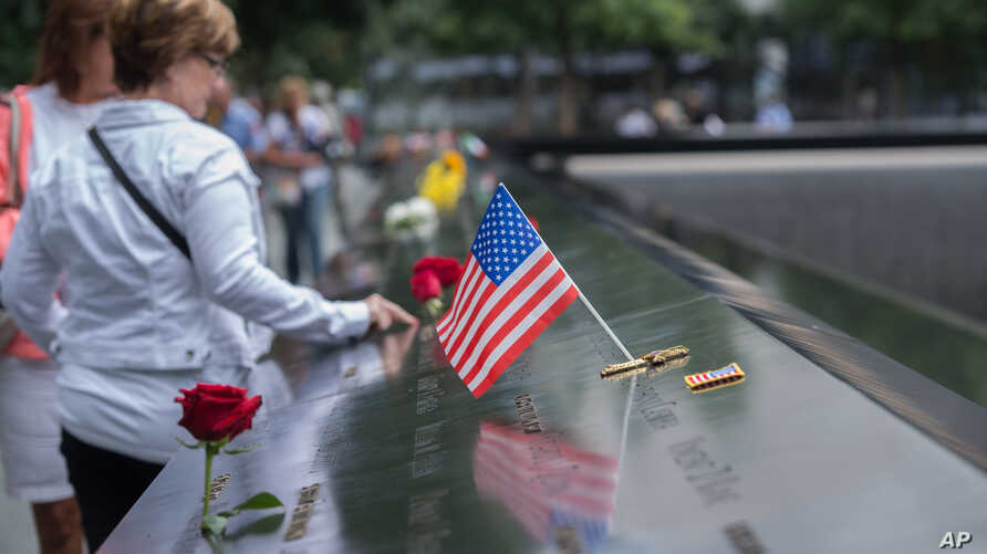 Visitors touch the names of the victims of the Sept. 11, 2001, terror attacks at the South Pool of the National September 11 Memorial, Sept. 11, 2015, in New York.