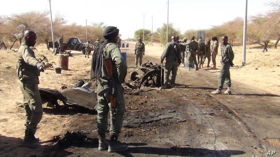 In this photo taken March 21, 2013, Malian soldiers stand around the debris left after a jihadist suicide bomber blew himself up at a Malian army checkpoint near the airport in Timbuktu, Mali.