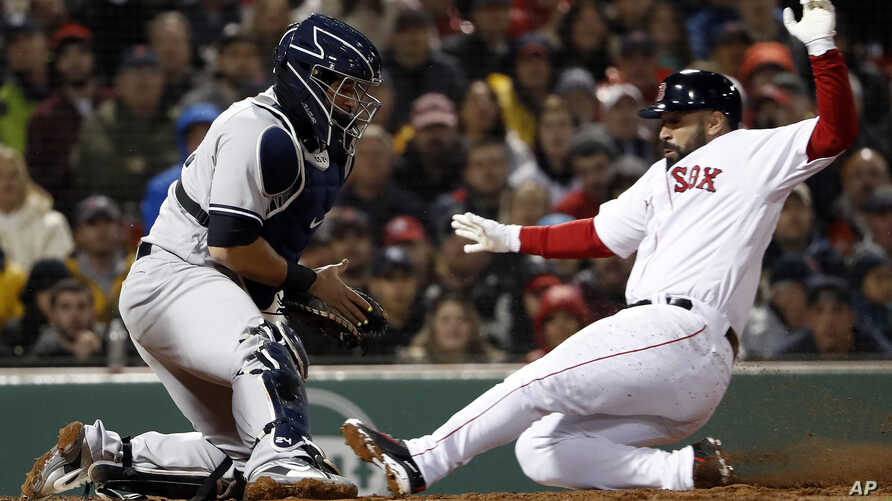 Boston Red Sox's Sandy Leon scores as New York Yankees catcher Gary Sanchez doesn't handle the throw during the second inning of a baseball game at Fenway Park in Boston on  April 12, 2018.