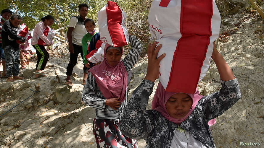 Residents affected by earthquake and tsunami carry aid provided during the visit of Indonesian President Joko Widodo in Donggala, north of Palu, Central Sulawesi, Indonesia, Oct. 3, 2018 in this photo taken by Antara Foto.