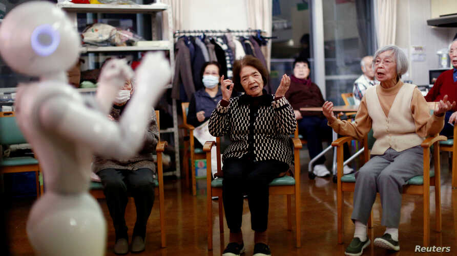 Residents follow moves made by humanoid robot 'Pepper' during an afternoon exercise routine at Shin-tomi nursing home in Tokyo, Feb. 2, 2018.